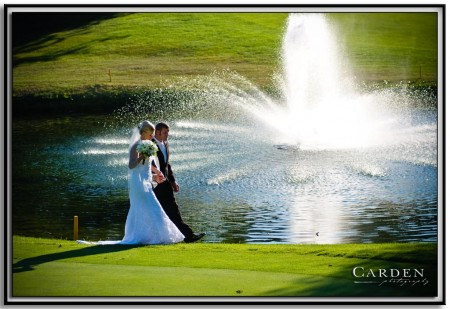 Bride and Groom at wedding on golf course by fountain.
